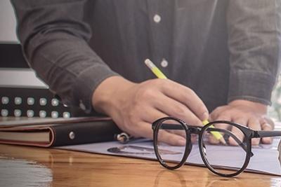 Mann schreibt mit gelbem Stift, Brille daneben